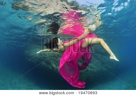 Beautiful woman underwater wrapped in pink fabric poster