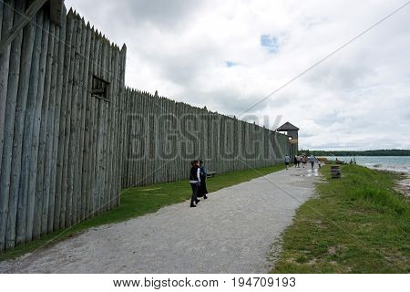 MACKINAW CITY, MICHIGAN / UNITED STATES - JUNE 18, 2017: Visitors walk towards the north entrance of Fort Michilimackinac, at the Colonial Michilimackinac State Park.