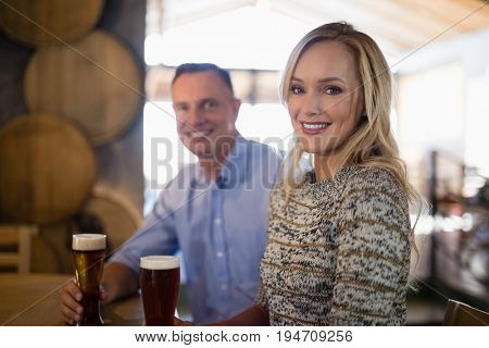 Portrait of happy couple holding glasses of beer in bar