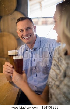 Smiling couple interacting with each other while having beer in bar