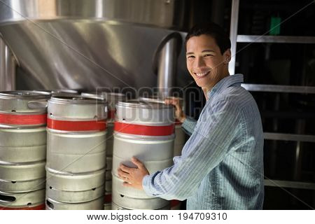 Portrait of manager checking beer keg in warehouse of restaurant