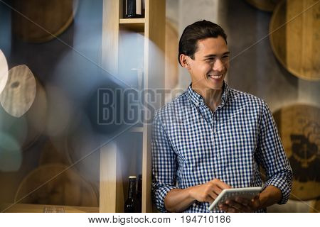 Bar tender using digital tablet at counter in restaurant