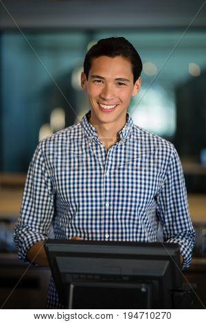 Portrait of bar tender operating cash desk at counter in restaurant