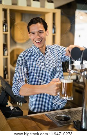 Portrait of bar tender filling beer from beer pump at bar counter in restaurant