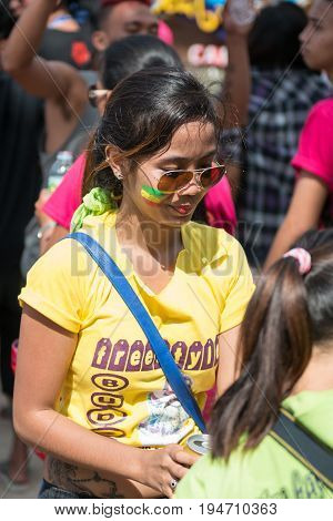 Filipino girl with face painted and yellow shirt celebrating Ati-Atihan Festival at White Beach.
