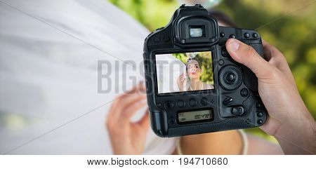 Cropped hand of photographer holding camera  against bride blowing soap bubbles