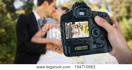 Cropped hand of photographer holding camera  against newlywed couple kissing besides wedding cake