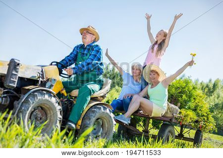 Senior man taking waving family for ride on tractor trailer across countryside field in summer