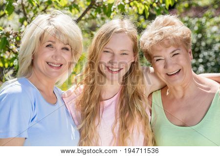 Three generations of women. Family spending time together in the garden, hugging and smiling.