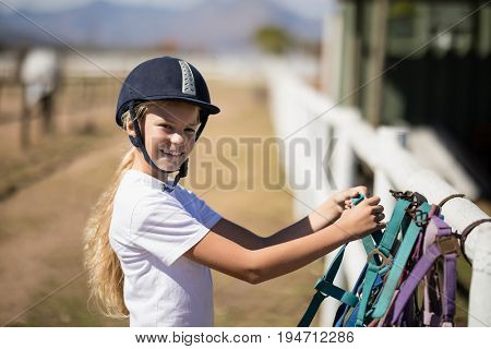 Portrait of smiling girl picking up a horse muzzle in the ranch