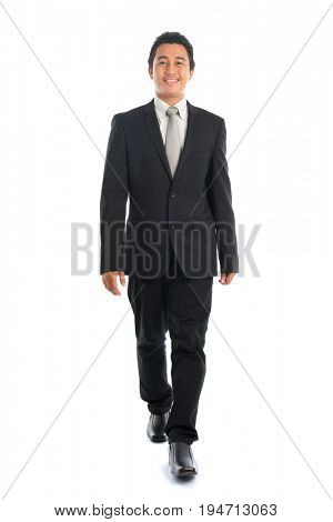 Full body front view portrait of attractive young Southeast Asian businessman walking, isolated on white background.