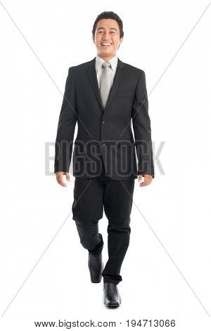 Full body front view portrait of happy young Southeast Asian businessman walking, isolated on white background.