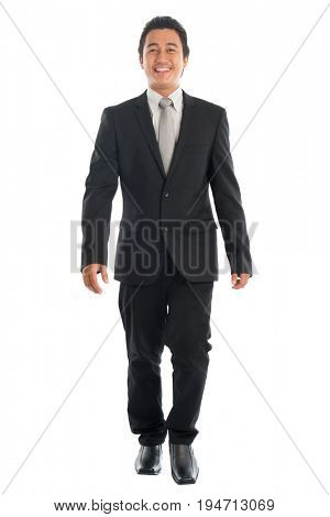 Full body front view portrait of good looking young Southeast Asian businessman walking, isolated on white background.