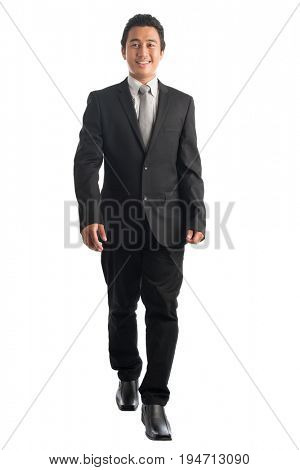 Full body front view portrait of handsome young Southeast Asian businessman walking, isolated on white background.