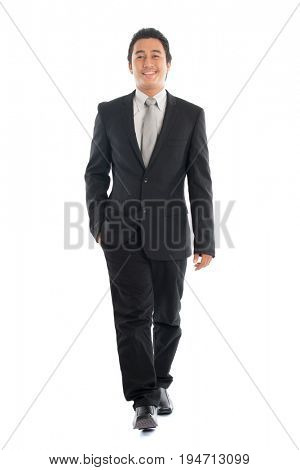 Full body front view portrait of young Southeast Asian businessman walking, isolated on white background.