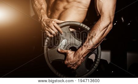 man in gym. Muscular bodybuilder guy doing exercises with barbell. Strong person with Tense strong male hand with veins barbell. Flare for text and design.