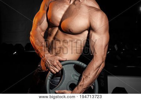 man in gym. Muscular bodybuilder guy doing exercises with barbell. Strong person with Tense male hand with veins barbell. Modern journal toning.