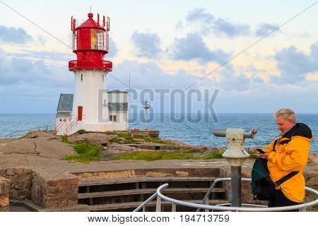 Male tourist traveler looking at historic red white lighthouse on the edge of rocky sea coast South Norway Lindesnes Fyr beacon