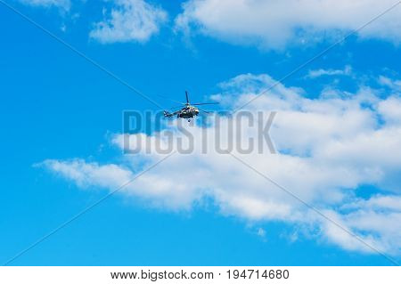 A civilian rescue helicopter flies close to the ground against a blue sky and cirrus clouds.
