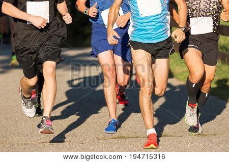 The leaders of a 5K summer race running in a tight pack about three quarters of a mile into the race on a black top path.