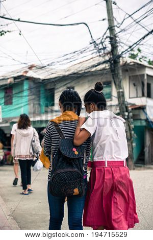 BORACAY, WESTERN VISAYAS, PHILIPPINES - JANUARY 12, 2015: Two girl friends walking in a normal street of Boracay.
