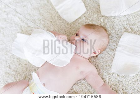 Cute adorable newborn baby of 3 months with diapers. Happy tiny little girl or boy looking at the camera. Dry and healthy body and skin for children concept. Baby nursery