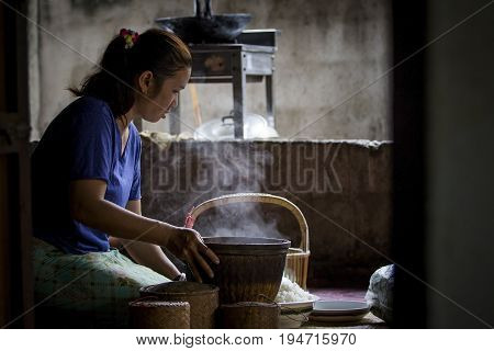 MAHASARAKHAM THAILAND - JULY82017 : thai north eastern woman prepare steaming sticky rice from bamboo basket for all day meal sticky rice most faverite and main food for thai north eastern