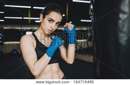 Pretty young girl in sportswear standing in combat position. Sporty woman has wrapped her fists with blue bandage tape. Close up
