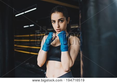 Aggressive girl standing in combat or defence position near the punching bag. Focused sporty woman looking right at the camera. Close up