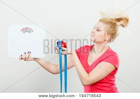 Woman Holding Apple,measuring Tape And Weight Machine