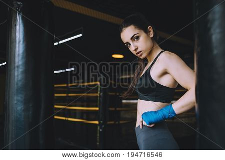 Attractive young woman standing between two punching bags with left hand on her waist and looking with confidence. Profile view. Close up