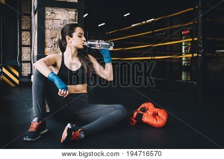 Weary attractive girl drinking a bottle with water sitting near window on the floor in the dark gym with red boxing gloves beside her.