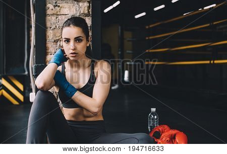 Serious sportive woman is scratching her neck with right hand and weary looking at the camera while resting after training. Close up