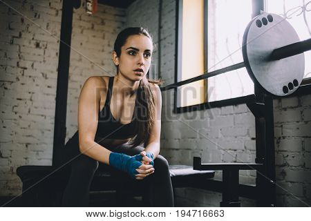 Tired beautiful woman with wrapped hands with blue bandage tape sitting on the bench near the window and preparing for the fighting. Close up