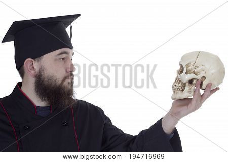 Young man in a graduate cap with a skull on a white background