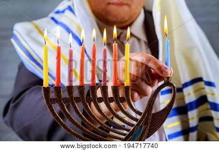 Hanukkah, a Jewish celebration. Candles burning in the menorah, the man in the background.