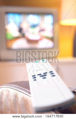Remote control on leather armchair with television in background