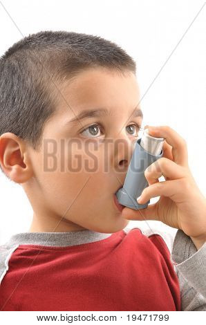 Close up image of a cute little boy using inhaler by himself for asthma. White background vertical studio picture.