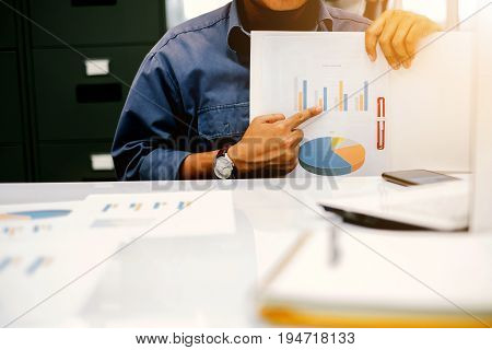 Young businessmen presenting graphs at the quarterly performance report over blurred office. select focus and Film Tone with Light fair