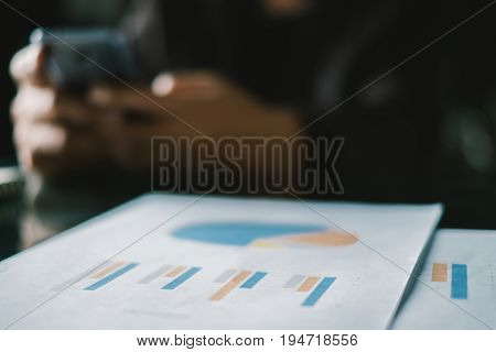 Young businessmen analyze graphs to meet goals set over blurred Business graph on the table in office .Film tones and Light fair