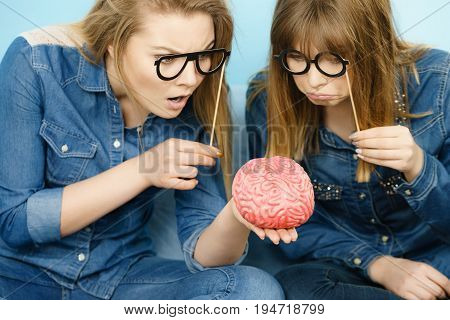 Two serious women friends or sisters wearing jeans shirts and eyeglasses on stick thinking about solving problem holding fake brain