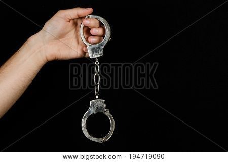 Men's hand holds the iron handcuffs isolated on a black background. The concept of justice and fairness