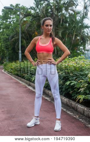 Full-length portrait of sporty fit model standing in park posing in pink sports bra and white leggings with hands on hips