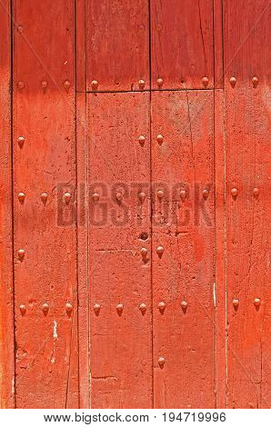 Cherry coloured stained ancient door with studs and planking