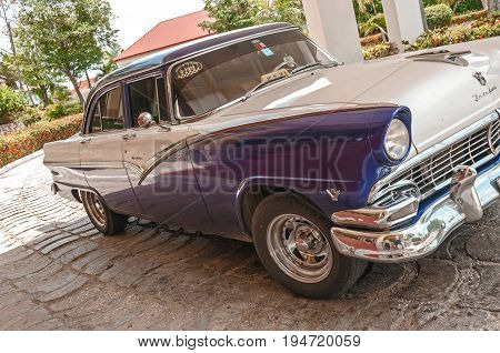 Guardalavaca,Cuba - June 16, 2015: Classic 1950's American Taxi, One of countless vintage US made cars imported to Cuba before the Revolution but still running after more than 50 years ,waiting outside hotel for a fare.