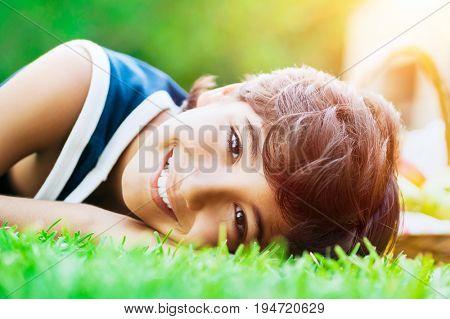 Portrait of cute joyful boy lying down on the fresh green grass in bright sunny day, enjoying happy summer vacation in the summer camp