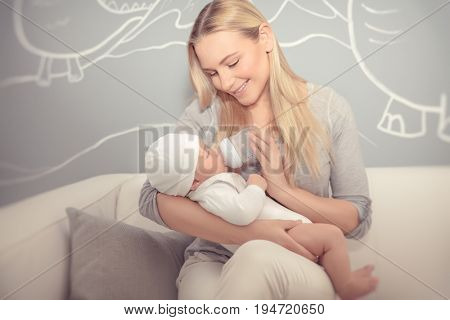 Cute mother feeding her adorable newborn baby in the beautiful cozy kid's room at home, special milk formula for infants, enjoying parenthood, happy family life