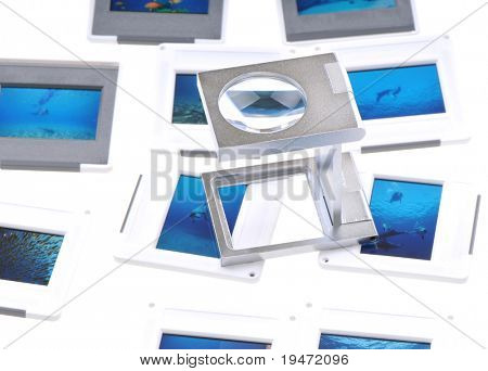 White background studio image of a lightbox with slides and a loupe.