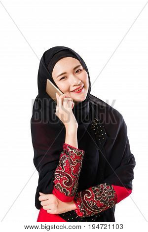 Beautiful young muslim woman using moblie phone on a white background.