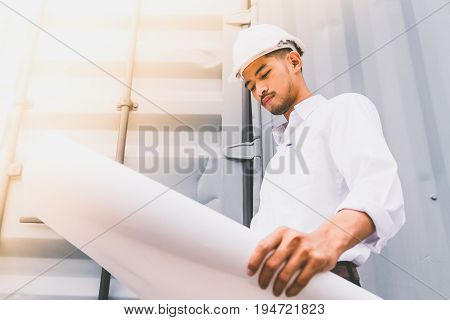 Civil engineer holding blueprint at the construction site.